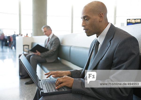 Geschäftsmann mit Laptop im Loungebereich des Flughafens
