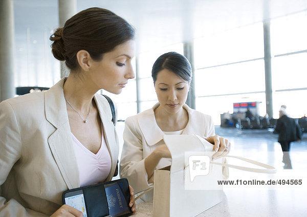 Zwei Geschäftsfrauen auf der Suche nach dem Geldbeutel am Flughafen