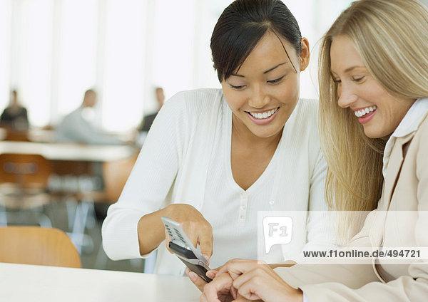 Zwei junge Geschäftsfrauen schauen gemeinsam aufs Handy
