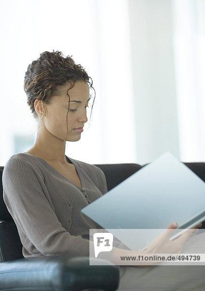 Junge Geschäftsfrau sitzt und schaut sich die Akte an