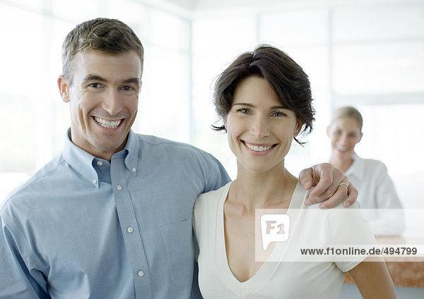 Paar lächelnd  Rezeption im Hintergrund