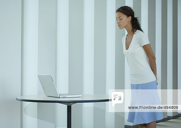 Frau stehend  schaut auf Laptop auf Tisch Frau stehend, schaut auf Laptop auf Tisch