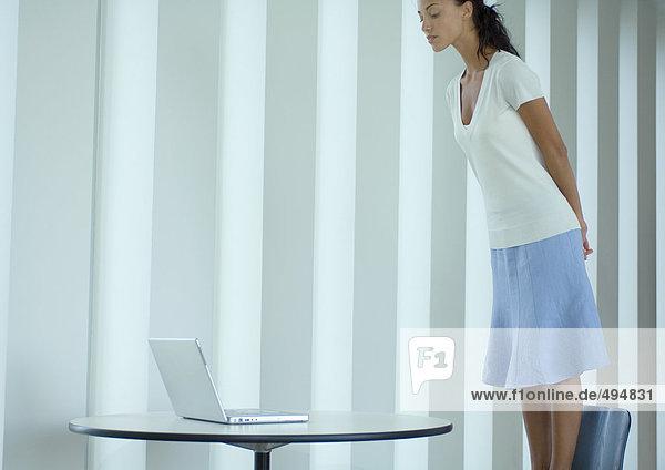 Frau steht auf einem Stuhl und schaut auf den Laptop. Frau steht auf einem Stuhl und schaut auf den Laptop.