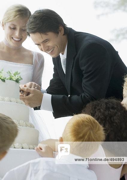 Bräutigam schneidet Hochzeitstorte