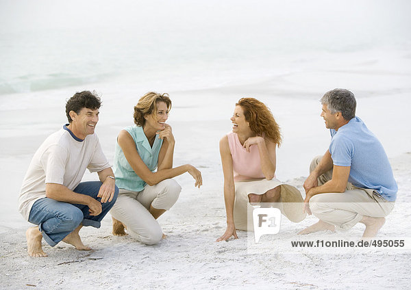 Two mature couples crouching on beach
