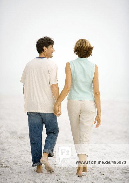 Reife Paare gehen Hand in Hand am Strand  Rückansicht