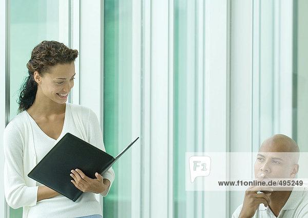 Frau mit lächelndem Programm  während der männliche Kollege denkt. Frau mit lächelndem Programm, während der männliche Kollege denkt.