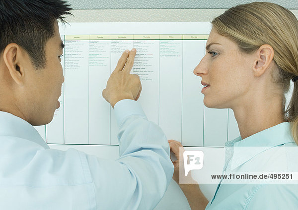 Two office workers looking at chart on wall