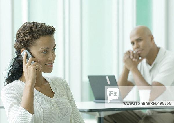Frau benutzt Handy  während der Mann sie im Hintergrund beobachtet. Frau benutzt Handy, während der Mann sie im Hintergrund beobachtet.