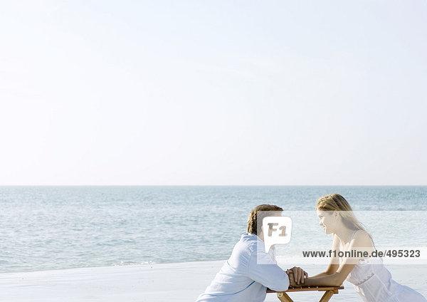 Ein Paar sitzt am Strand und schaut sich an.