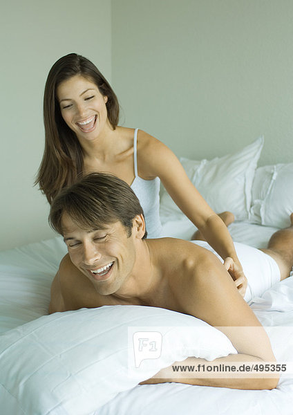 Woman tickling man in bed