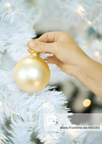 Kind legt Ornament auf den Weihnachtsbaum