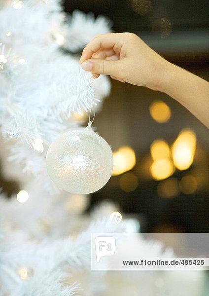 Kind hängender Weihnachtsschmuck am Baum