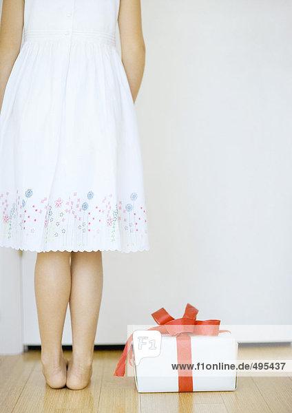 Mädchen steht neben dem Geschenk