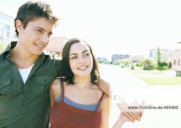 Junges Paar beim Spaziergang in der Wohngegend