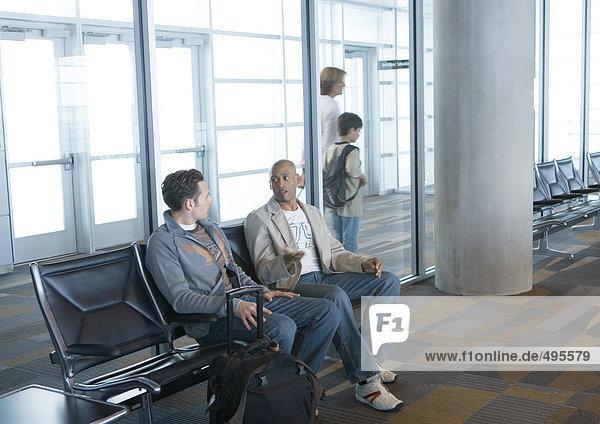Zwei Männer sitzen in der Flughafenlounge,  Reisende gehen im Hintergrund vorbei.