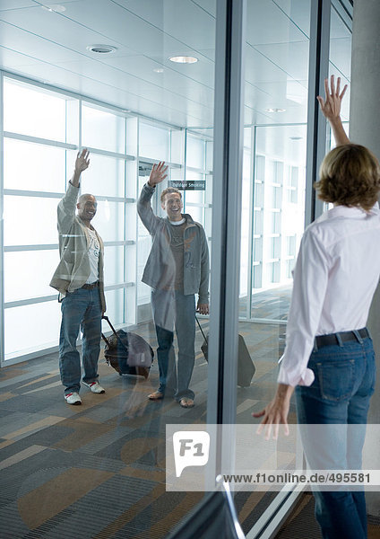 Männliche Reisende winken der Frau durch das Fenster am Flughafen zu.