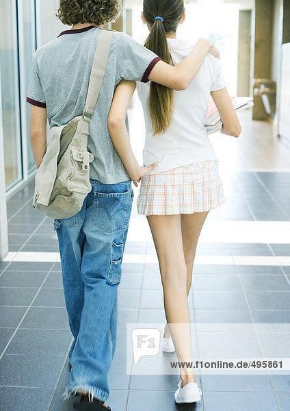 Teen couple walking in school hallway  rear view