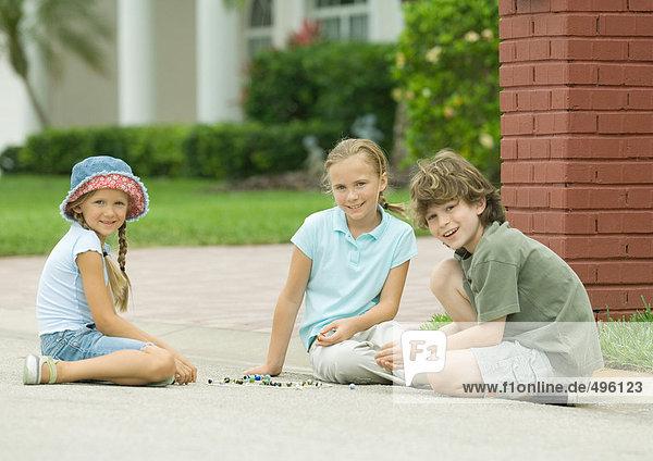 Drei Kinder beim Murmeln im Freien