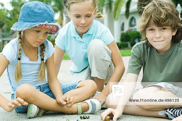 Kinder spielen Murmeln in der Wohnstraße