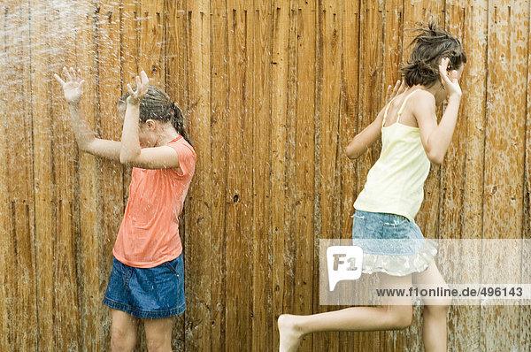 Mädchen werden nass in der Sprinkleranlage