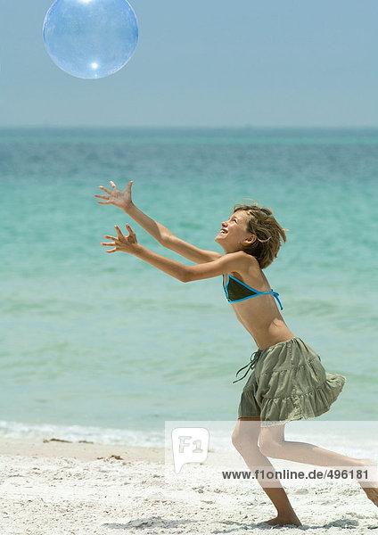 Mädchen fangen Strandball am Strand