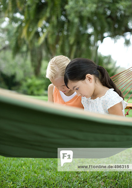 Two girls sitting in hammock together