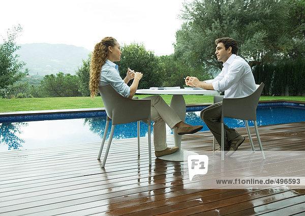 Frau und Mann sitzen im Freien am Pool und arbeiten