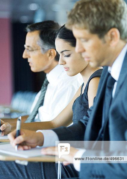 Geschäftsleute beim Sitzen  die sich Notizen machen