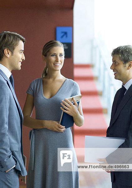 Drei Geschäftsleute  die stehen und reden.