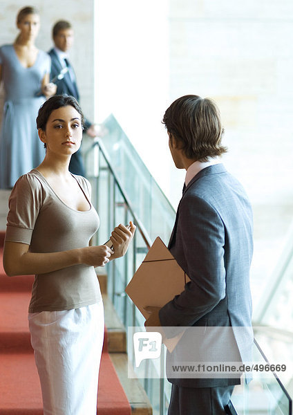 Businessman and woman talking on stairs