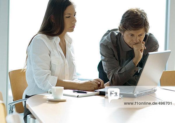 Geschäftsfrau und Mann bei der Arbeit mit dem Laptop