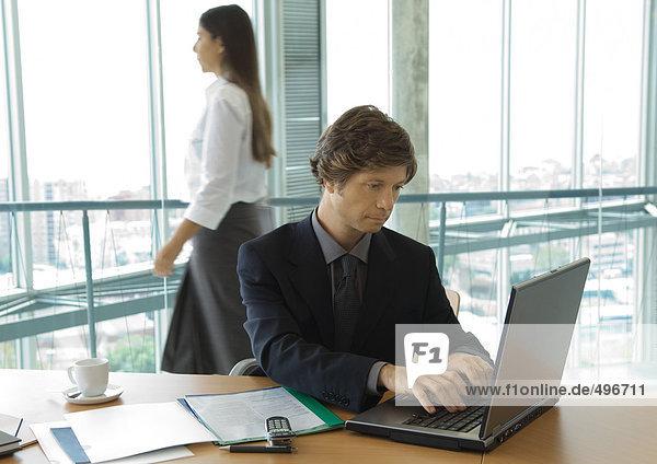Geschäftsmann mit Laptop  Frau im Hintergrund vorbeikommend