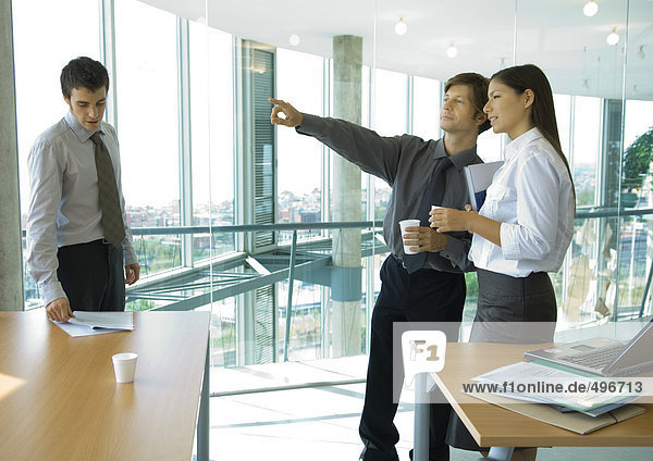 Geschäftskollegen stehen mit Tassen Kaffee  unterhalten sich