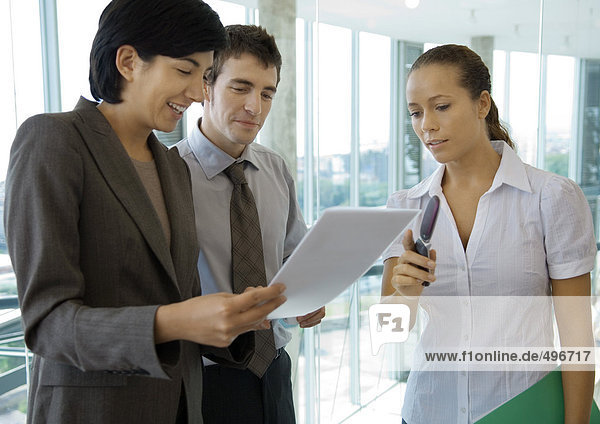 Business colleagues standing  discussing document