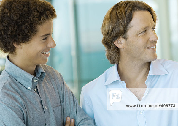 Male executive and office worker smiling  looking out of frame