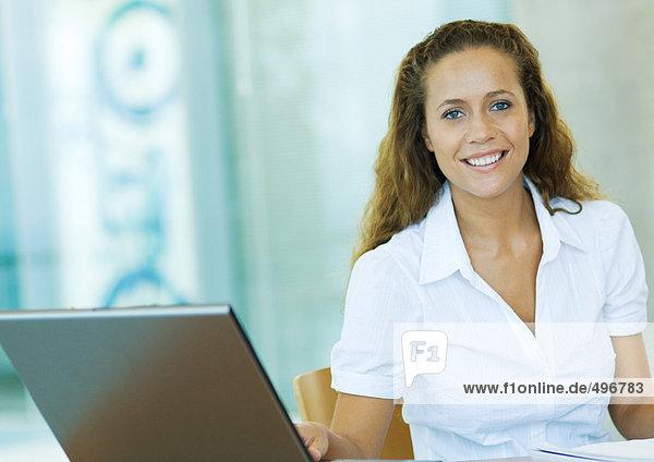 Businesswoman sitting by laptop  smiling  portrait