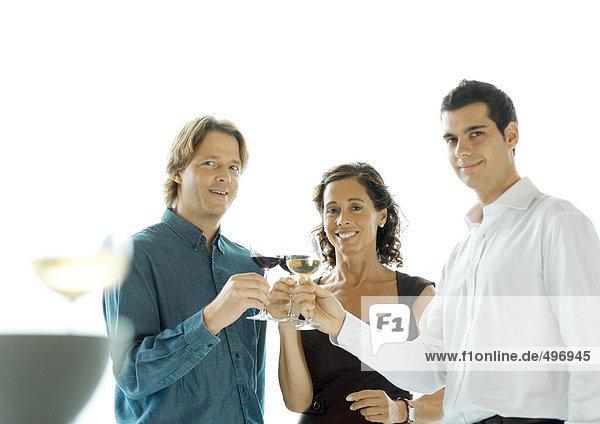 Leute  die mit einem Glas Wein anstoßen.