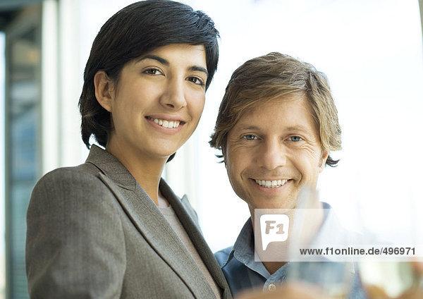 Männliche und weibliche Führungskraft  lächelnd  anstoßend