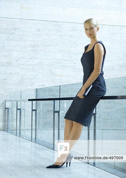 Geschäftsfrau an der Leitplanke gelehnt  Ganzkörperporträt