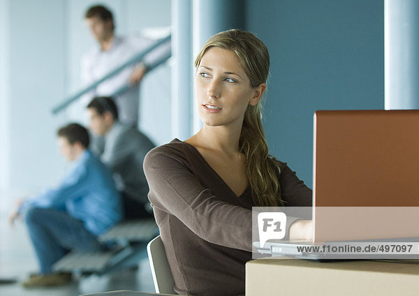 Woman using laptop on cardboard box  colleagues in background