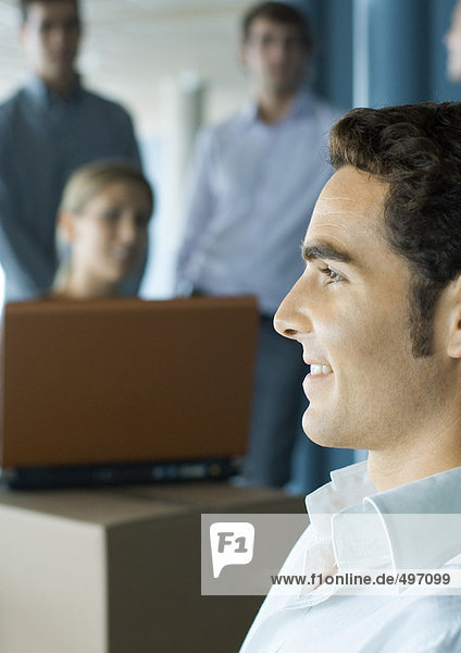 Young man smiling  profile  colleagues using laptop in background