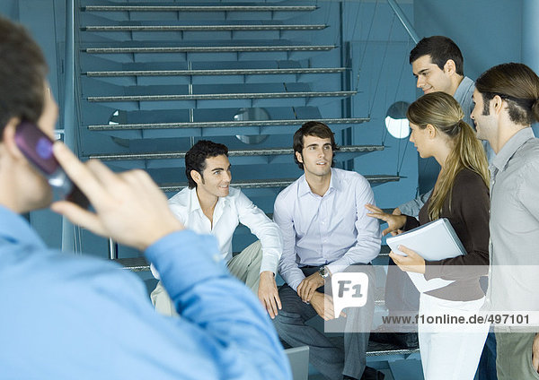 Eine Gruppe von Kollegen versammelte sich um die Treppe und unterhielt sich.