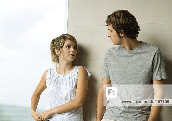 Junger Mann und Frau lehnen sich an die Wand.