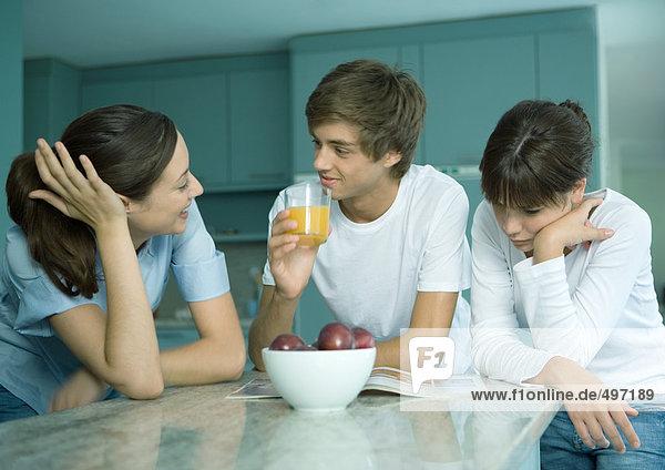 Frau und jugendliche Kinder stehen zusammen in der Küche und reden.