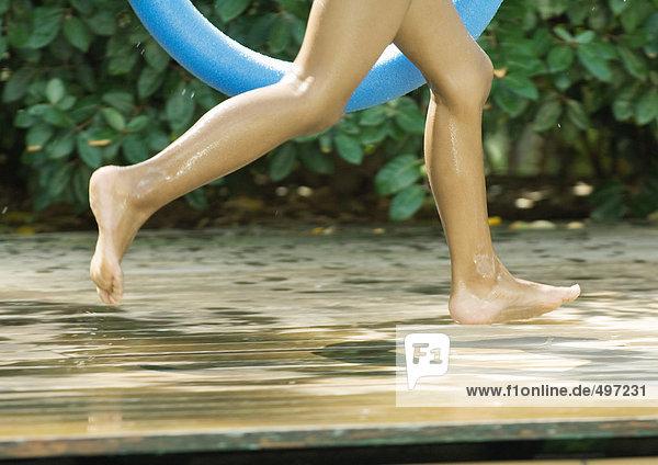 Kind läuft am Beckenrand  abgeschnittene Ansicht der Beine
