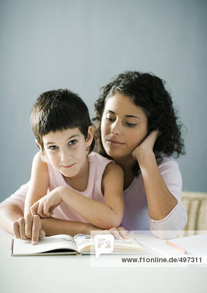 Mutter hilft Kind bei den Hausaufgaben