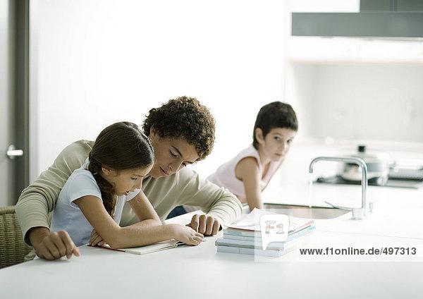 Teenager-Junge hilft jüngerer Schwester bei den Hausaufgaben