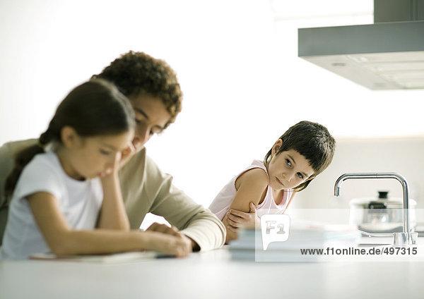 Teenager-Junge hilft jüngerer Schwester bei den Hausaufgaben  zweites Geschwisterkind beim Zuschauen