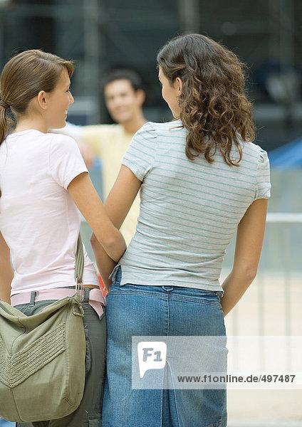 Teenager-Mädchen vor Teenager-Jungen  Rückansicht